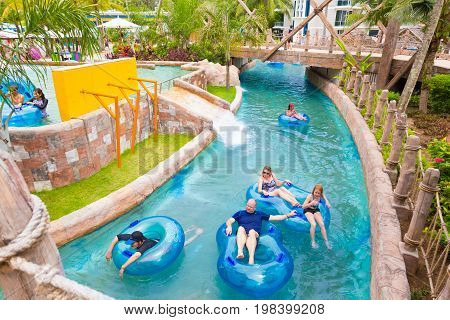 Phuket Thailand - 8 July 2017 - western family enjoy thier time riding water float tubes in Lazy River at Splash Jungle Water Theme Park in Phuket Thailand on July 8 2017