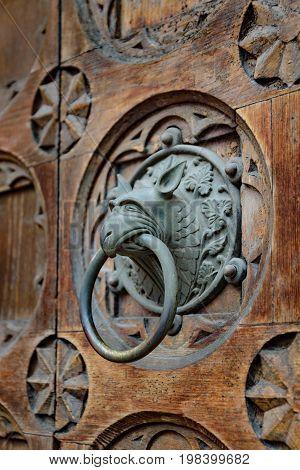 Antique door knocker shaped like monster's head.