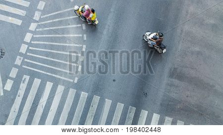 top aerial view of blur bikers ride the motorcycles to pass pedestrian crosswalk on road with the traffic pattern signage on the street.