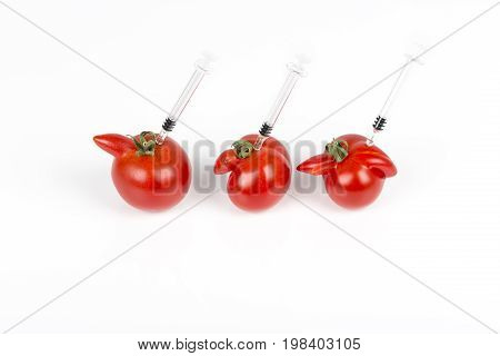 Tomatoes with deformation and defects with syringe. Chemical treatment for rapid maturation in tomatoes. Strange forms grown mutated tomatoes. Front and top view.