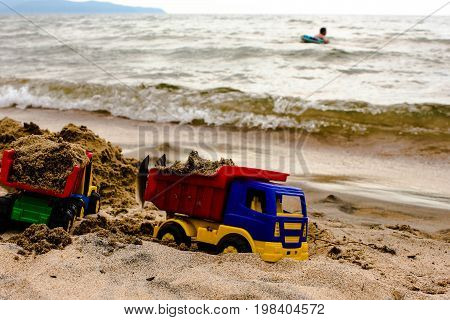 Beach with golden sand and childrens toy earthmover cars near the water with swimming child. Calm summer vacation photo