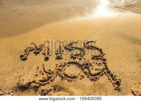 Sea or ocean lonely beach with miss you inscription on golden sunny sand. Separation summer vacation photo