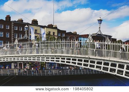 DUBLIN IRELAND - July 15th 2017: view of the historical Ha'Penny Bridge over the River Liffey in Dublin Ireland (with unidentified people)