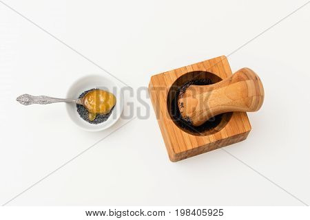 Poppy seed in pounder and honey teaspoon