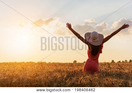 Beautiful Young Woman With Brown Hear Wearing Rose Dress And Hat With Raised Arms Enjoying Outdoors