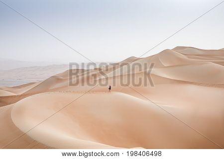 woman running down a dune in Rub al Khali Desert at the Empty Quarter in Abu Dhabi United Arab Emirates