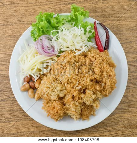 Thai Cuisine and Food Top View of Thai Traditional Crispy Catfish Salad Served With Green Oak Shredded Green Mango Red Onion Cabbage Chili and Peanut.