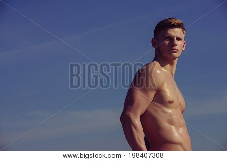 Athletic bodybuilder pose as hercules. Sport and workout. Gladiator or atlant. Man with muscular wet body. Adam with glitter on bare chest copy space