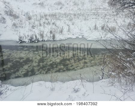 winter landscape. A small river among a winter snowstorm. Postcard with a river in winter. low temperature. Frozen river