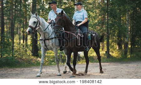 Kazan, Russia - 28 july 2017: Police - man and woman - on horses in forest, side view