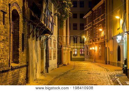 Narrow medieval street in old Riga, where city tourists can find a unique atmosphere of Middle Ages and famous ensembles of Gothic architecture