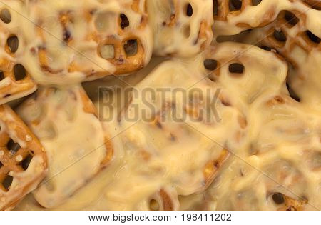 Close view of melted dipping cheese mixed with waffle pretzels.