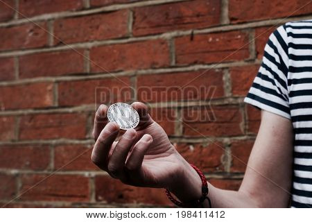 Digital currency physical silver litecoin coin on man hand