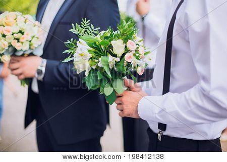Confident smiling handsome groom in black suit with groomsman having fun outdoor.