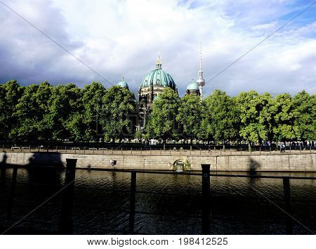 Berliner Dom behind trees with Spree river and cloudy sky