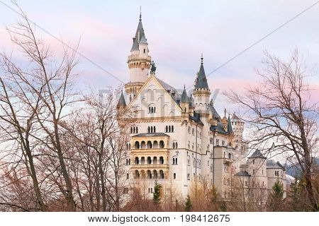 World-famous tourist attraction in the Bavarian Alps, fairytale Neuschwanstein or New Swanstone Castle, the 19th century Romanesque Revival palace at sunset, Hohenschwangau, Bavaria, Germany