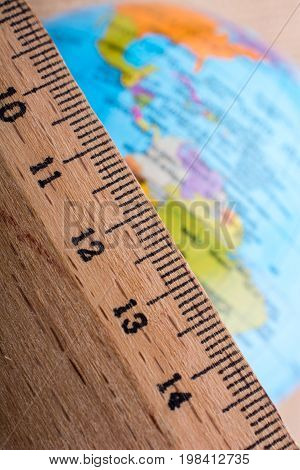 Globe Placed Beside A Wooden Ruler