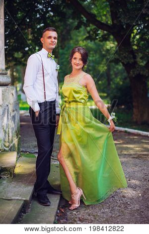 The bridesmaid and groomsman stand on the street