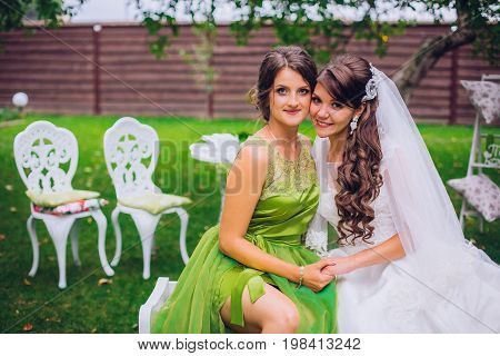 Bride and bridesmaid embracing in the park on the wedding day. Bridesmaid in green color dress.