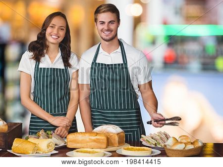 Digital composite of Bakery owners with food table against blurry background