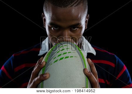 Close up portrait of male rugby player with ball against black background