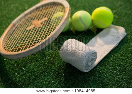 Close up of napkin with tennis balls and racket on field