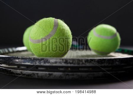 Close up of tennis balls on racket against blackbackground
