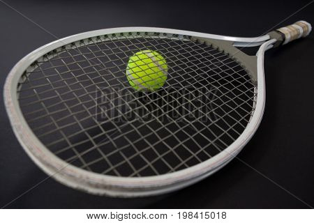 High angle view tennis racket on ball against black background