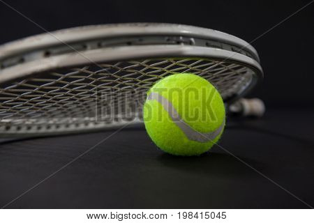 Close up of ball and silver tennis racket against black background