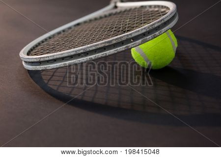 Close up of tennis racket on ball with shadow over black background