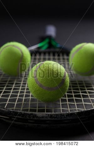 Close up of balls on tennis racket against black background