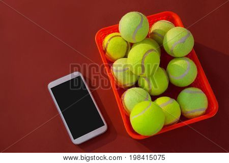 High angle view of tennis balls in red basket by mobile phone on maroon background