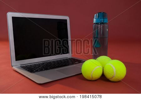 Close up of fluorescent yellow tennis balls by laptop and water bottle against maroon background