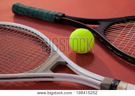 High angle view of fluorescent yellow ball amidst tennis rackets on maroon background