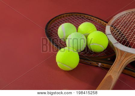 High angle view of tennis balls with wooden rackets on maroon background