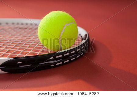 Close up of tennis ball on racket against maroon background