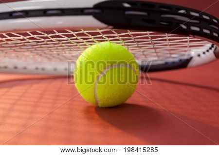 Close up of tennis racket leaning on ball against maroon background