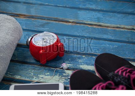High angle view of alarm clock by mobile phone amidst napkin and sports shoes on blue wooden table