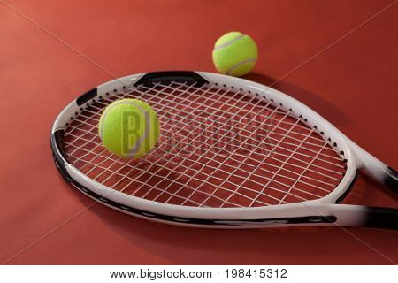 High angle view of tennis racket and fluorescent yellow balls against maroon background