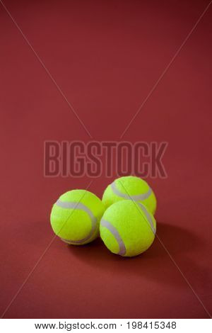 High angle view of three tennis balls on maroon background