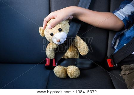 Mid-section of teenage boy sitting with teddy bear in the back seat of car
