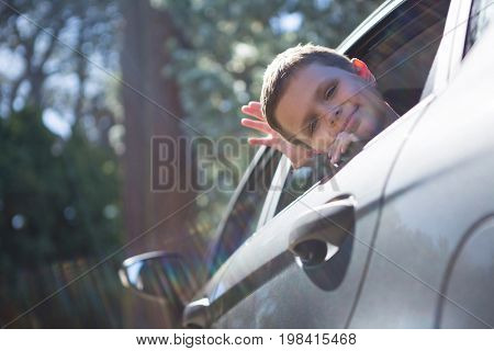 Teenage boy looking from open car window on a sunny day