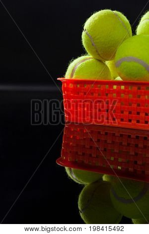 Close up of fluorescent yellow tennis balls in plastic basket with reflection against black background