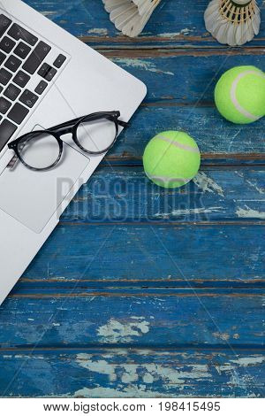 Overhead view of laptop and eyeglasses with shuttlecocks by tennis balls on blue wooden table