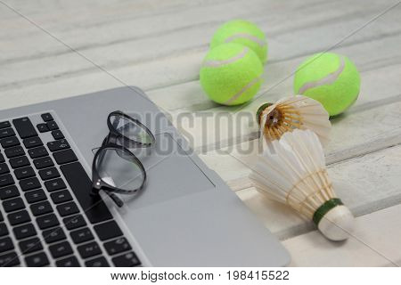 High angle view of eyeglasses on laptop by shuttlecocks and tennis balls on white wooden table
