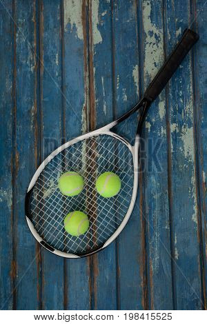 Overhead view of tennis racket and balls on blue wooden table