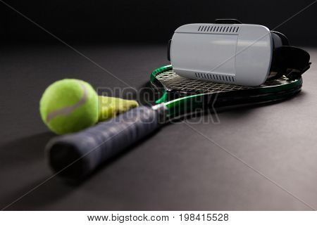Close up of virtual reality headset on tennis racket by ball against black background