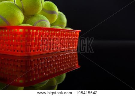 Pile of fluorescent yellow tennis balls in red plastic basket with reflection against black background