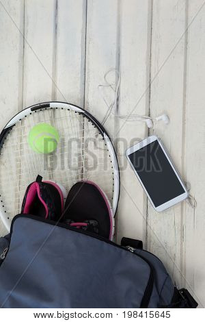 Overhead view of gray bag on sports shoes with tennis gear by mobile phone over white wooden table