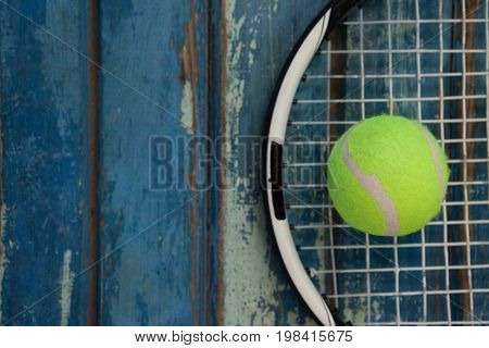 Overhead view of fluorescent yellow tennis ball on racket over blue wooden table